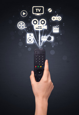 out of control: Hand holding a remote control, media icons coming out of it Stock Photo