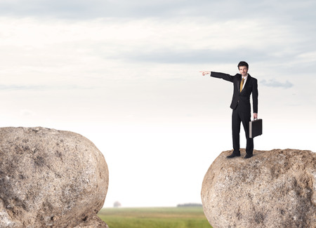 bridging: Young businessman standing on edge of rock mountain