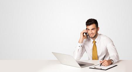 white laptop: Uomo d'affari seduto al tavolo bianco con un computer portatile bianco su sfondo bianco