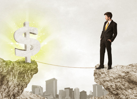 bridging: Businessman standing on the edge of mountain with a shining dollar mark on the other side