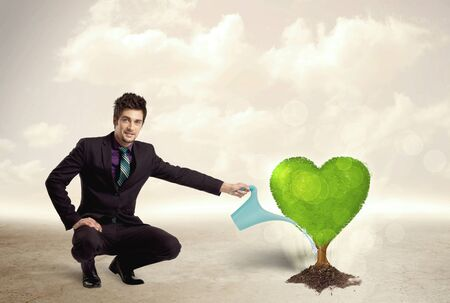 adore: Business man watering heart shaped green tree concept on background