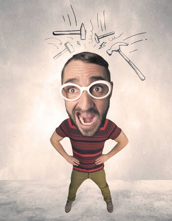 exaggeration: Funny person with big head and drawn punching hammers over it Stock Photo