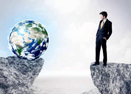 bridging the gaps: Businessman standing on the edge of mountain with a globe on the other side Stock Photo