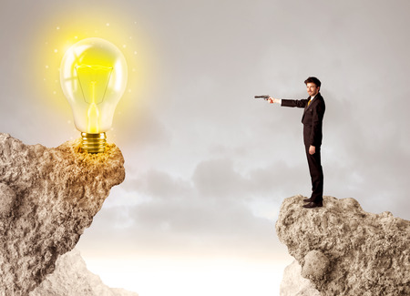 bridging the gap: Businessman standing on the edge of mountain with an idea bulb on the other side