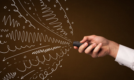 out of control: Hand holding a remote control, curly lines and arrows coming out of it Stock Photo