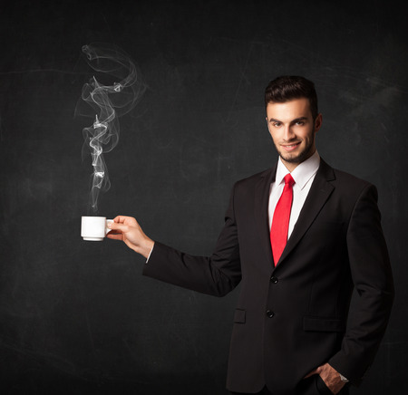 steamy: Businessman standing and holding a white steamy cup on a black background Stock Photo