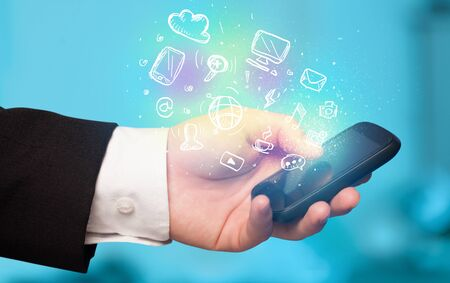 smartphone in hand: Hand holding smartphone with glowing multimedia icons Stock Photo