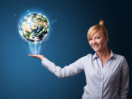 Young businesswoman holding in her hand a glowing earth globe photo