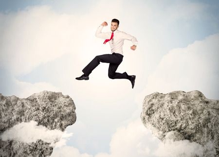 cliff jumping: Happy business man jumping over a cliff concept Stock Photo