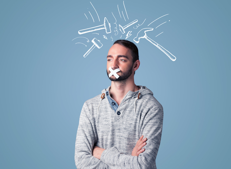 hammer head: Young man with taped mouth and white drawn beating hammer marks around his head Stock Photo