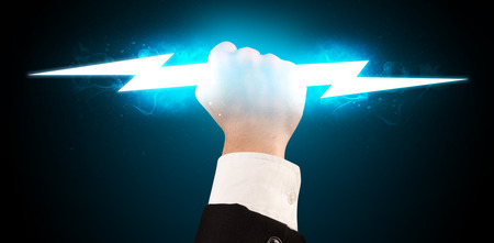 lightning storm: Business man holding glowing lightning bolt in his hands concept Stock Photo