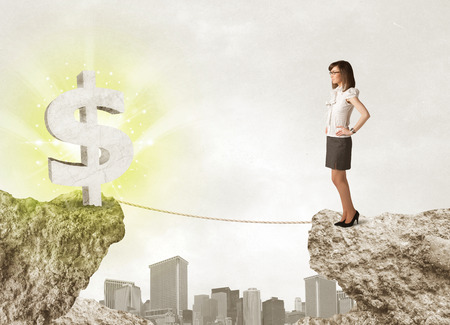 bridging: Businesswoman standing on the edge of mountain with a shining dollar mark on the other side