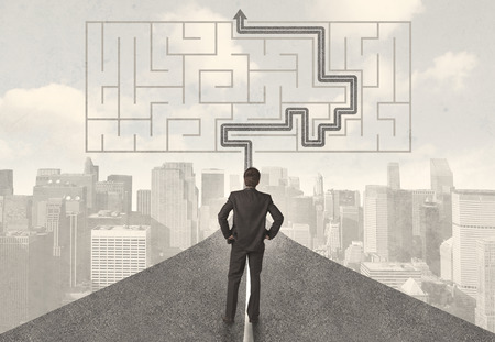 complicated journey: Businessman looking at road with maze and solution concept