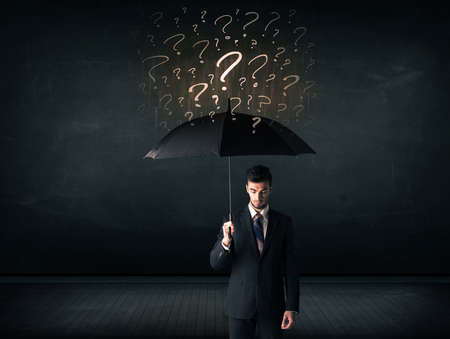 shielding: Businessman with umbrella and a lot of drawn question marks concept on background Stock Photo