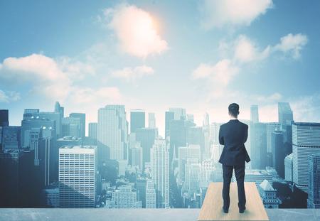 屋根の上に立って、未来都市を見ての実業家 写真素材