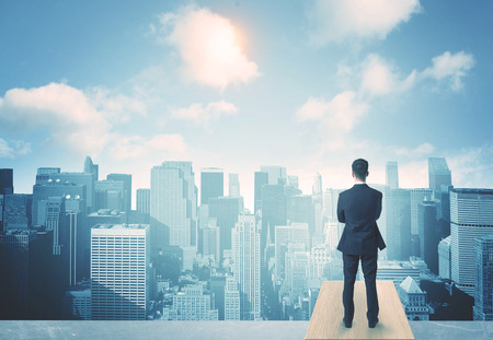 Businessman standing on a roof and looking at future city Standard-Bild