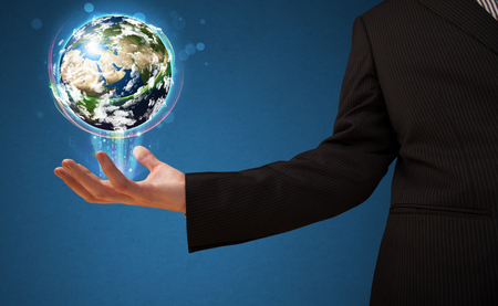 businessman carrying a globe: Young businessman holding in his hand a glowing earth globe,