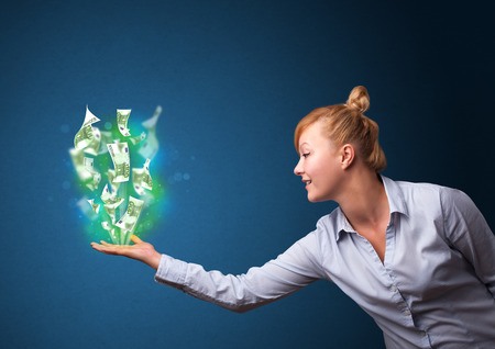 Young businesswoman holding glowing paper moneys in her hand photo