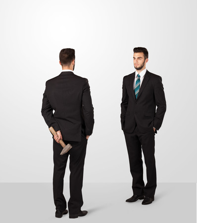 opposing: Two opposing businessman shake hands, one of them hiding a weapon behind his back