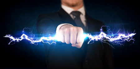 control power: Business man holding electricity light bolt in his hands concept