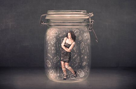 computer writing: Business woman captured in glass jar with hand drawn media icons concept on background