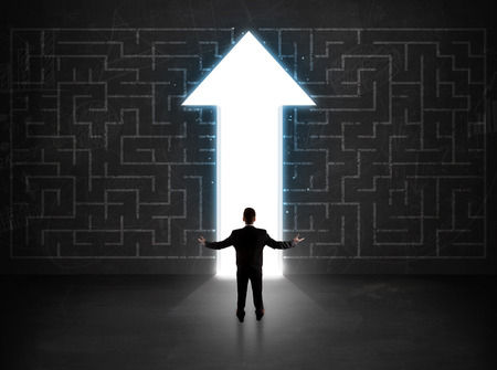 person looking: Business person looking at maze with solution arrow on the wall concept