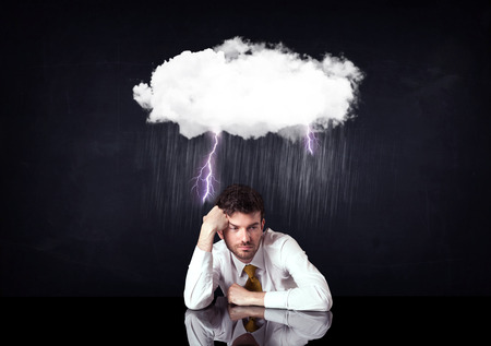 rain weather: Depressed businessman sitting under a lightning rainy cloud Stock Photo