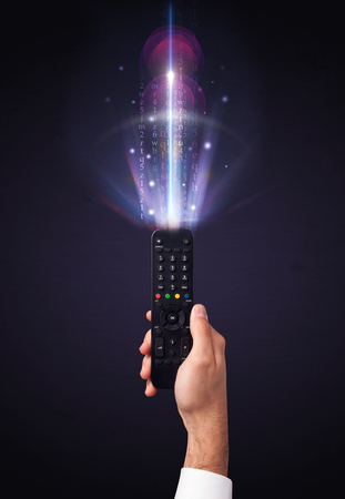 out of control: Hand holding a remote control, shining numbers and letters coming out of it