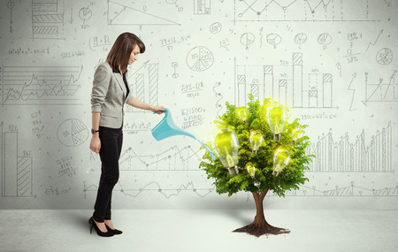 growing inside: Business woman pouring water on lightbulb growing tree concept