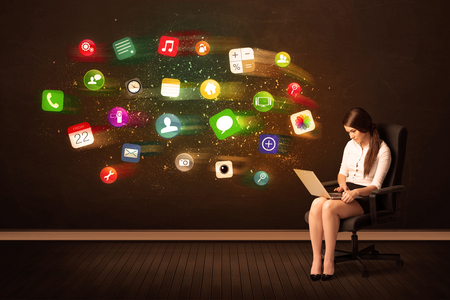 background information: Business woman sitting in office chair with laptop and colorful app icons concept on background