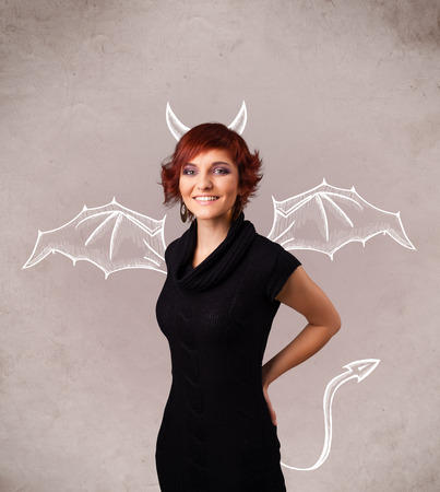 Young nasty girl with devil horns and wings drawing photo