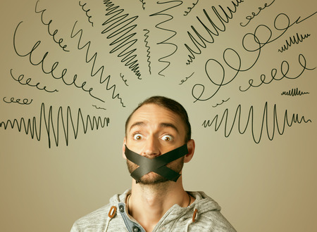 keep an eye on: Young man with taped mouth and curly lines around his head Stock Photo