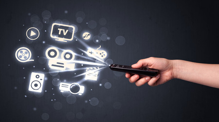 remote: Hand holding a remote control, media icons coming out of it Stock Photo