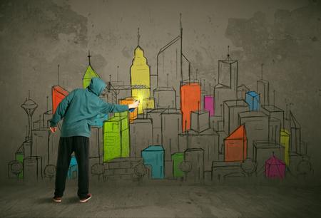 pintor: Pintor joven urbana dibujo colorido de la ciudad en la pared