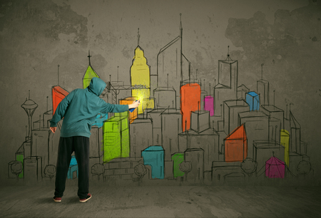 painter: Young urban painter drawing colorful city  on the wall