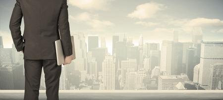 Üzletember hátulról előtt egy városra néző az ablakon Stock fotó