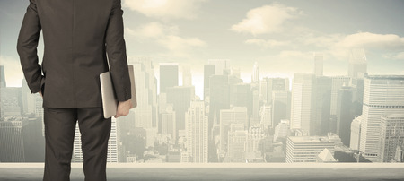 empresario: Hombre de negocios de la parte de atrás frente a una vista de la ciudad en la ventana Foto de archivo