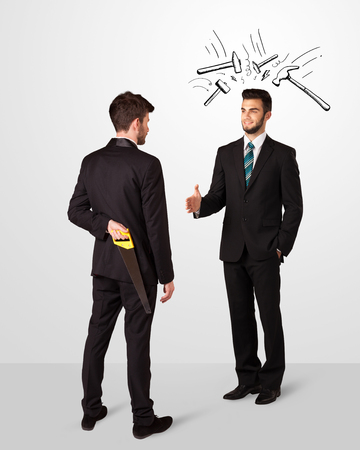 unethical: Ruthless businessman hiding a weapon white drawn beating hammer marks Stock Photo