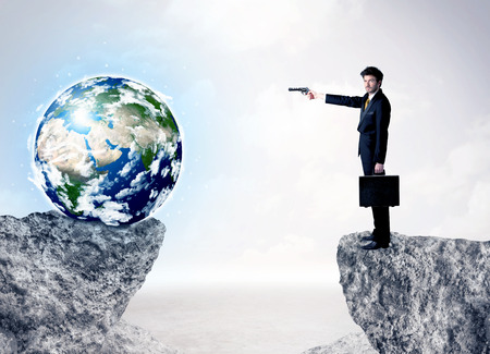 to the other side: Businessman standing on the edge of mountain with a globe on the other side Stock Photo