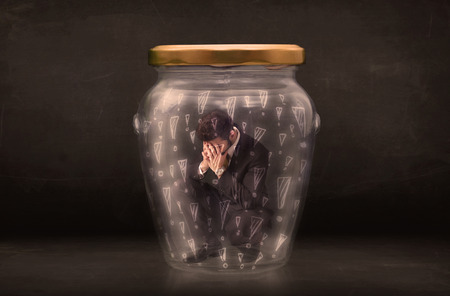 suffocating: Business man trapped in jar with exclamation marks concept on bakcground