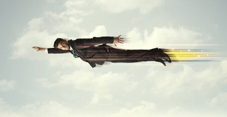 man flying: Happy business man flying fast on the sky between clouds concept