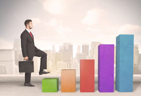 man climbing: Business person climbing up on colourful chart pillars concept on city background