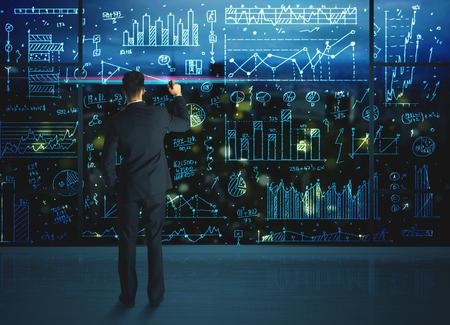 ガラスの壁にビジネスの統計情報を図面の実業家 写真素材