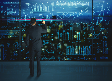 gerente: Dibujo estad�sticas de las empresas sobre la pared de vidrio del hombre de negocios