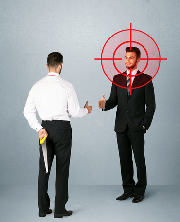 immoral: Ruthless businessman handshake with a hiding weapon and a head target point
