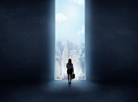 puerta abierta: empresaria de pie delante de la enorme puerta Foto de archivo