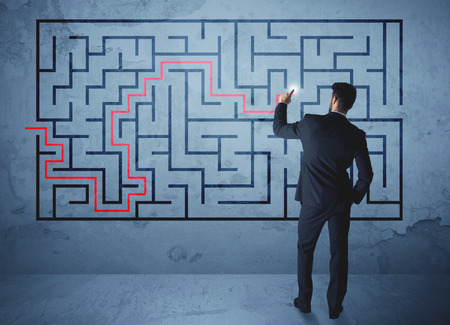 solve problem: Businessman finding the solution of a maze Stock Photo