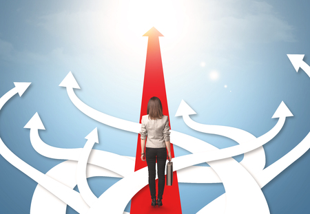 Concept of confused businesswoman with different direction arrows Standard-Bild
