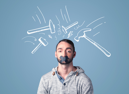 sellotape: Young man with taped mouth and white drawn beating hammer marks around his head Stock Photo