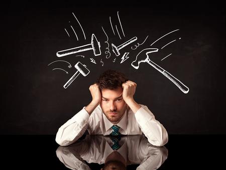 Jonge depressieve zakenman zittend onder wit getrokken kloppende hamer merken Stockfoto